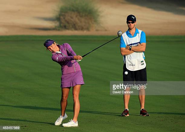 Danielle Montgomery of England plays her second shot on the par 5 10th hole watched by her caddie John Peers of Australia the tennis player during...