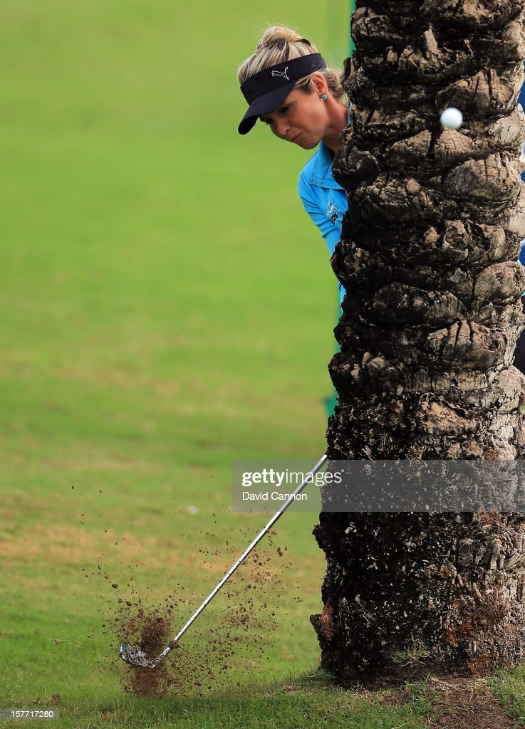 Danielle Montgomery of England plays her third shot from behind a palm tree at the par 4, 9th hole during the second round of the 2012 Omega Dubai Ladies Masters on the Majilis Course at the Emirates Golf Club on December 6, 2012 in Dubai, United Arab Emirates.