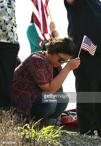 Danielle Potter joins with others holding American flags across the highway from the strip mall where a gunman attacked the Armed Forces Career...
