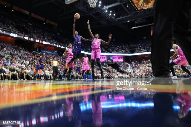 Danielle Robinson of the Phoenix Mercury drives to the basket defended by Jonquel Jones of the Connecticut Sun and Alyssa Thomas of the Connecticut...