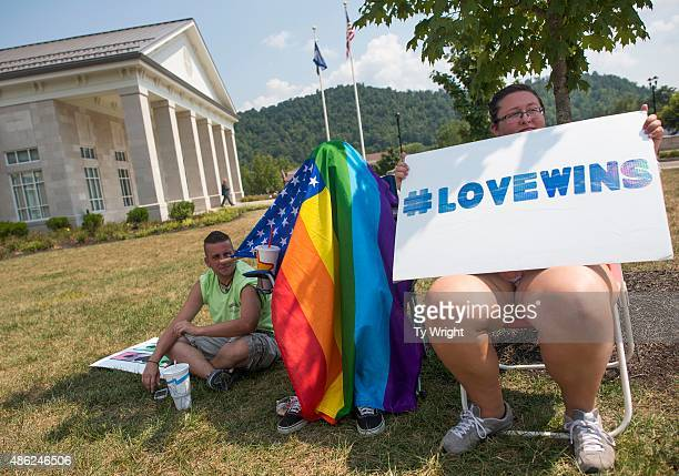 Danielle Wheeler holding a sign supporting same sex marriage fellow Morehead University student Darbi Hardin shading herself from the sun under the...