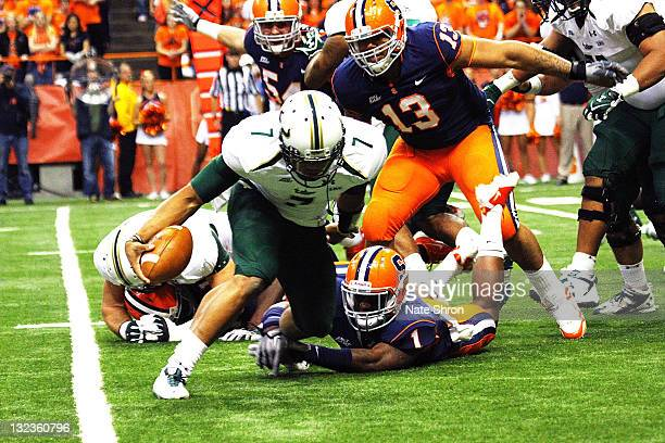 J Daniels of the South Florida Bulls runs the ball as he is tackled by Syracuse Orange players Phillip Thomas and Deon Goggins during the game at the...