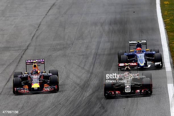 Daniil Kvyat of Russia and Infiniti Red Bull Racing drives next to Pastor Maldonado of Venezuela and Lotus and Felipe Nasr of Brazil and Sauber F1...