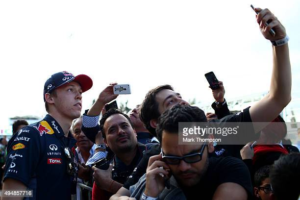 Daniil Kvyat of Russia and Infiniti Red Bull Racing poses for photographs with fans in the pit lane during previews to the Formula One Grand Prix of...