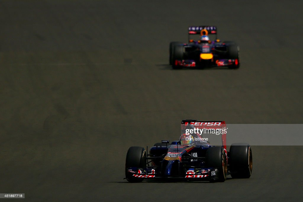 Daniil Kvyat of Russia and Scuderia Toro Rosso drives ahead of Sebastian Vettel of Germany and Infiniti Red Bull Racing during day two of testing at Silverstone Circuit on July 9, 2014 in Northampton, England.