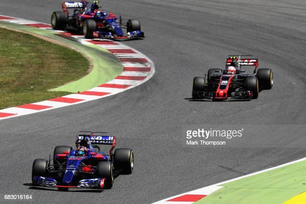 Daniil Kvyat of Russia driving the Scuderia Toro Rosso STR12 Kevin Magnussen of Denmark driving the Haas F1 Team HaasFerrari VF17 Ferrari and Carlos...