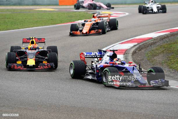 Daniil Kvyat of Russia driving the Scuderia Toro Rosso STR12 leads Max Verstappen of the Netherlands driving the Red Bull Racing Red BullTAG Heuer...