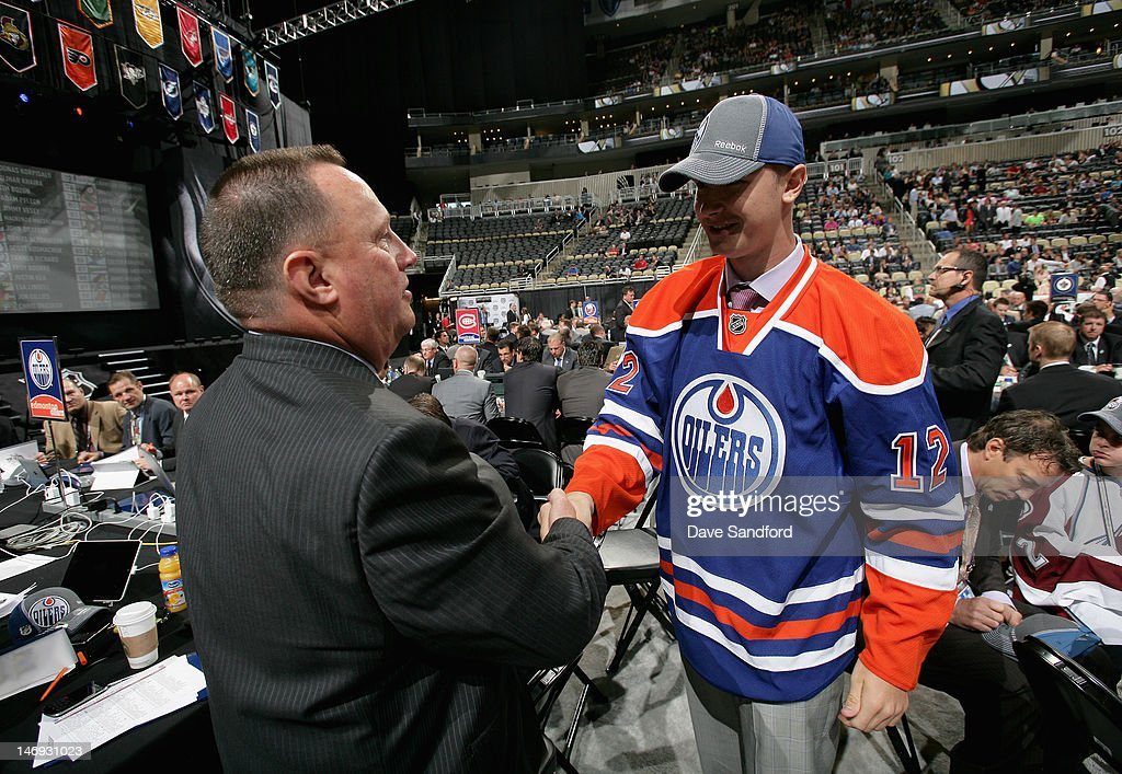 Daniil Zharkov, drafted 91st overall by the Edmonton Oilers greets head amateur scout Stu MacGregor during day two of the 2012 NHL Entry Draft at Consol Energy Center on June 23, 2012 in Pittsburgh, Pennsylvania.