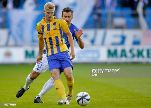 Daniils Turkovs of FK Ventspils is challenged by Magne Hoseth of Molde FK during their match in the second qualifying round for UEFA Champion League...