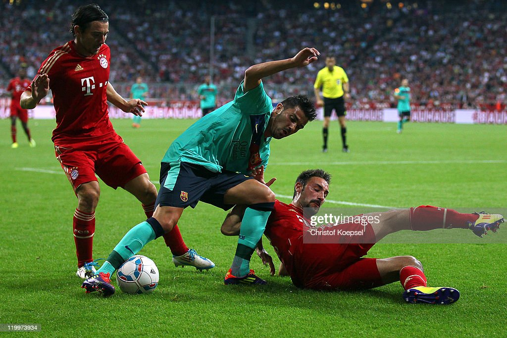 <a gi-track='captionPersonalityLinkClicked' href=/galleries/search?phrase=Danijel+Pranjic&family=editorial&specificpeople=698546 ng-click='$event.stopPropagation()'>Danijel Pranjic</a> of Bayern (L) and <a gi-track='captionPersonalityLinkClicked' href=/galleries/search?phrase=Diego+Contento&family=editorial&specificpeople=4336912 ng-click='$event.stopPropagation()'>Diego Contento</a> of Bayern (R) challenge <a gi-track='captionPersonalityLinkClicked' href=/galleries/search?phrase=David+Villa&family=editorial&specificpeople=467566 ng-click='$event.stopPropagation()'>David Villa</a> of Barcelona (C) during the Audi Cup final match between FC Bayern Muenchen and FC Barcelona at Allianz Arena on July 27, 2011 in Munich, Germany.