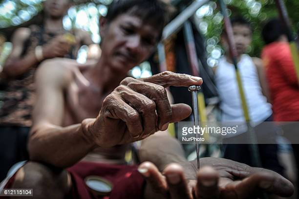 Danillo Castro who has been nailed to the cross every year since he was 20 shows a 5inch nail that will be used in his crucifixion during Good Friday...
