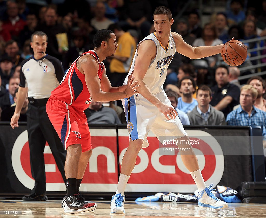Danilo Gallinari #8 of the Denver Nuggets controls the ball against Devin Harris #34 of the Atlanta Hawks at the Pepsi Center on March 4, 2013 in Denver, Colorado. The Nuggets defeated the Hawks 104-88.