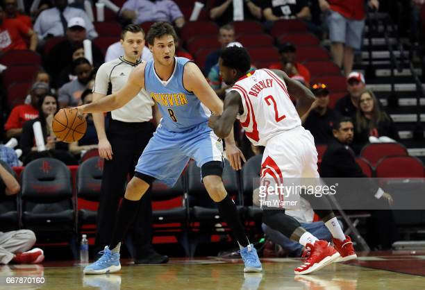 Danilo Gallinari of the Denver Nuggets controls the ball defended by Patrick Beverley of the Houston Rockets in the first half at Toyota Center on...
