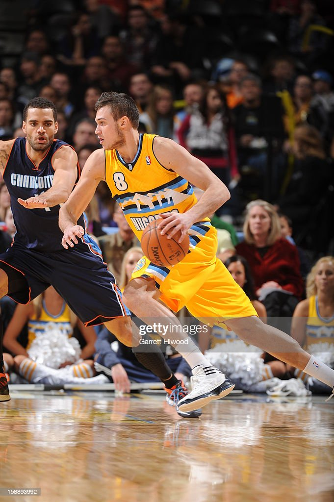 Danilo Gallinari #8 of the Denver Nuggets drives against Jeffery Taylor #44 of the Charlotte Bobcats on December 22, 2012 at the Pepsi Center in Denver, Colorado.