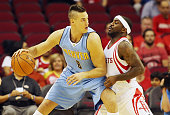 Danilo Gallinari of the Denver Nuggets drives with the basketball against Ty Lawson of the Houston Rockets during their game at the Toyota Center on...