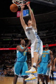 Danilo Gallinari of the Denver Nuggets dunks over AlFarouq Aminu of the New Orleans Hornets at the Pepsi Center on January 9 2012 in Denver Colorado...