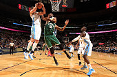 Danilo Gallinari of the Denver Nuggets grabs a rebound away from Greg Monroe of the Milwaukee Bucks and Kenneth Faried of the Denver Nuggets at Pepsi...