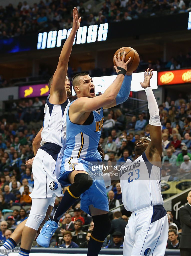 Danilo Gallinari of the Denver Nuggets is fouled by Wesley Matthews of the Dallas Mavericks during the first half at American Airlines Center on...