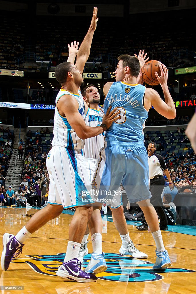 Danilo Gallinari #8 of the Denver Nuggets looks to pass the ball against Xavier Henry #4 and Ryan Anderson #33 of the New Orleans Hornets on March 25, 2013 at the New Orleans Arena in New Orleans, Louisiana.