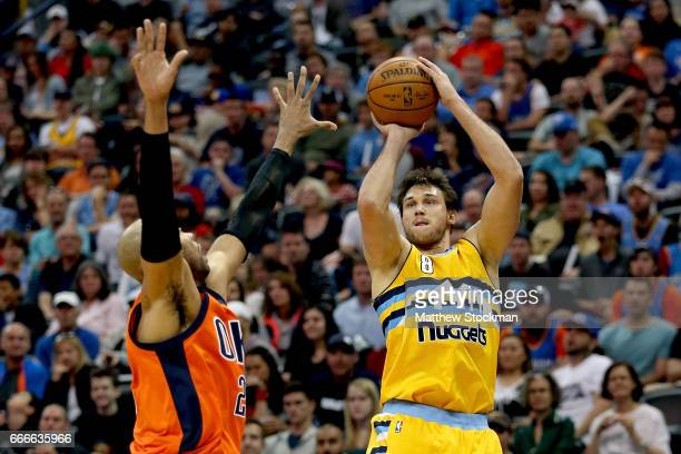 Danilo Gallinari of the Denver Nuggets puts up a shot over Taj Gibson of the Oklahoma City Thunder at Pepsi Center on April 9 2017 in Denver Colorado...