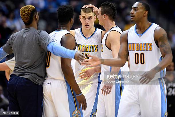 Danilo Gallinari of the Denver Nuggets rubs the head of Nikola Jokic after he walks off the court for a timeout during the second half of the...