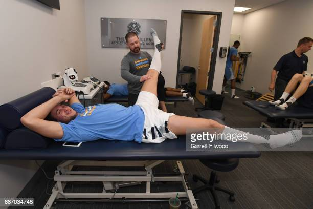 Danilo Gallinari of the Denver Nuggets stretches out with the athletic trainer before the game against the Los Angeles Lakers on March 13 2017 at the...