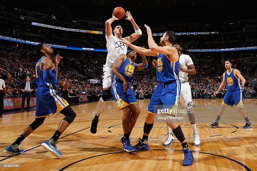 Danilo Gallinari of the Denver Nuggets tries to get off a shot over Brandon Rush and Andrew Bogut of the Golden State Warriors at Pepsi Center on...