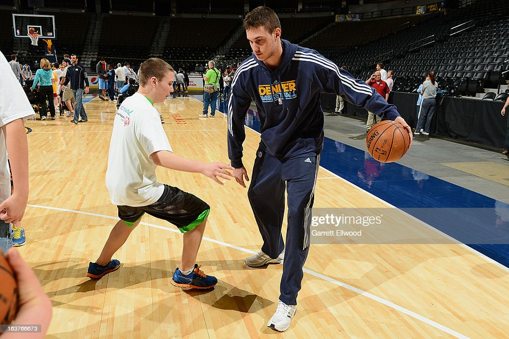 Danilo Gallinari #8 of the Denver Nuggets works with a special olympian during the annual Denver Nuggets/Special Olympics Basketball Clinic on March 14, 2013 at the Pepsi Center in Denver, Colorado.