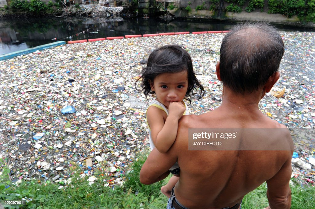 Danilo Laniada, 54, bearing his granddaughter Chazny, narrates how the garbage stinks as it floats down the San Juan river in Manila on January 11, 2013. The city's trash disposal agency traps solid waste floating down waterways that were thrown into the water by residents of slums along riverbanks upstream. AFP PHOTO / Jay DIRECTO