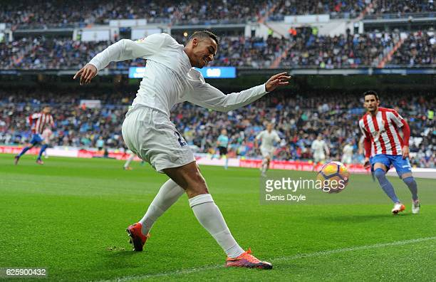 Danilo of Real Madrid crosses the ball in front of Isma Lopez of Sporting Gijon during the La Liga match between Real Madrid CF and Real Sporting de...