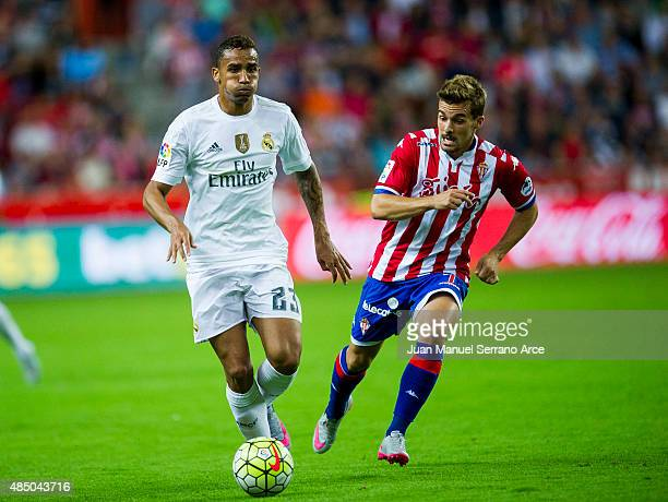 Danilo of Real Madrid duels for the ball with Juan Muniz of Real Sporting de Gijon during the La Liga match between Sporting Gijon and Real Madrid at...
