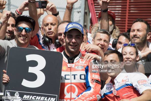 Danilo Petrucci of Italy and Octo Pramac Yakhnich celebrates the third place with team under the podium at the end of the MotoGP race during the...