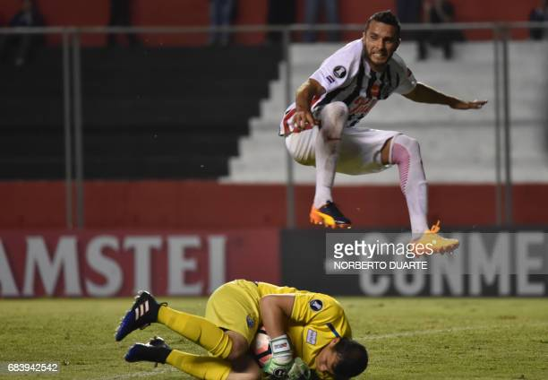 Danilo Santacruz of Paraguay's Libertad jumps over Bolivia's Sport Boy goalkeeper Miguel Mercado during their 2017 Copa Libertadores football match...