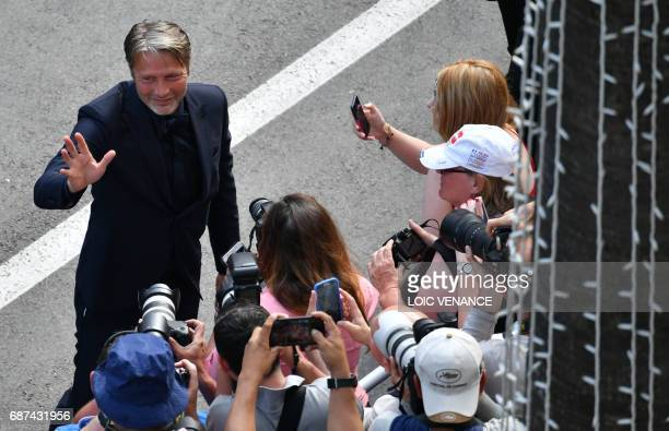 Danish actor Mads Mikkelsen poses for fans as he arrives on May 23 2017 for the '70th Anniversary' ceremony of the Cannes Film Festival in Cannes...