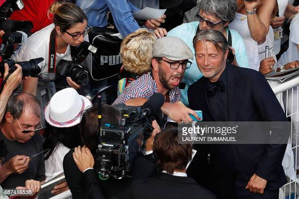 Danish actor Mads Mikkelsen poses for selfies with fans as he arrives on May 23 2017 for the '70th Anniversary' ceremony of the Cannes Film Festival...