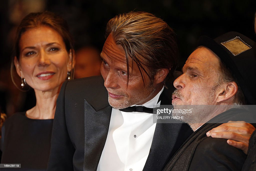 Danish actor Mads Mikkelsen (C) speaks with French actor Denis Lavant as they arrive on May 24, 2013 for the screening of the film 'Michael Kohlhaas' presented in Competition at the 66th edition of the Cannes Film Festival in Cannes. Cannes, one of the world's top film festivals, opened on May 15 and will climax on May 26 with awards selected by a jury headed this year by Hollywood legend Steven Spielberg. AFP PHOTO / VALERY HACHE