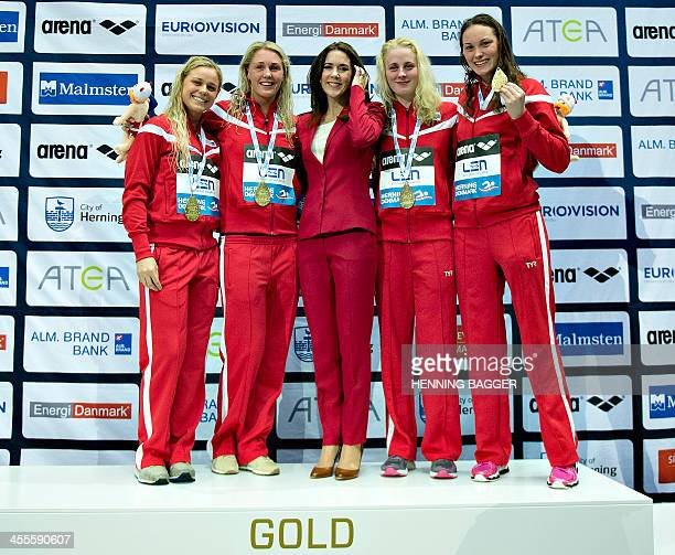 Danish Crown Princess Mary poses with athletes of Denmark's team celebrating on the podium after winning the women's 4x50 meters freestyle event of...