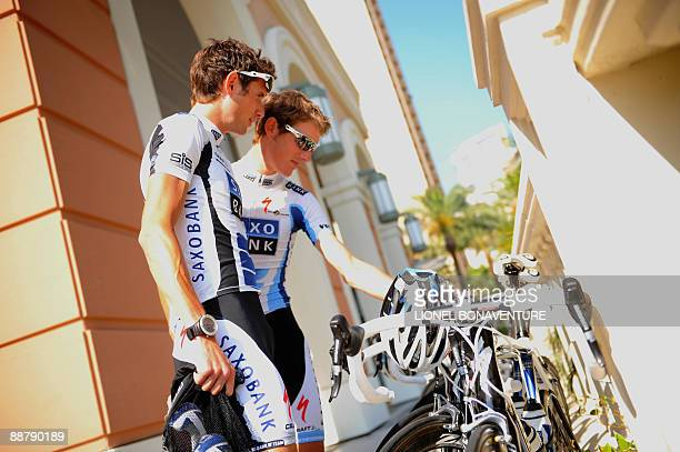 Danish cycling team Team Saxo Bank 's rider Andy Schleck of Luxemburg and teammate and brother Frank Schleck of Luxemburg look at their bikes in...