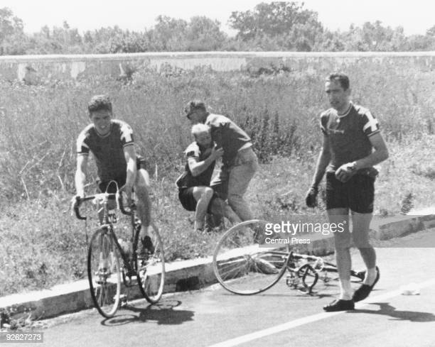 Danish cyclist Knud Enemark Jensen is carried unconscious to the side of the road by a Danish official after collapsing with heat stroke and...