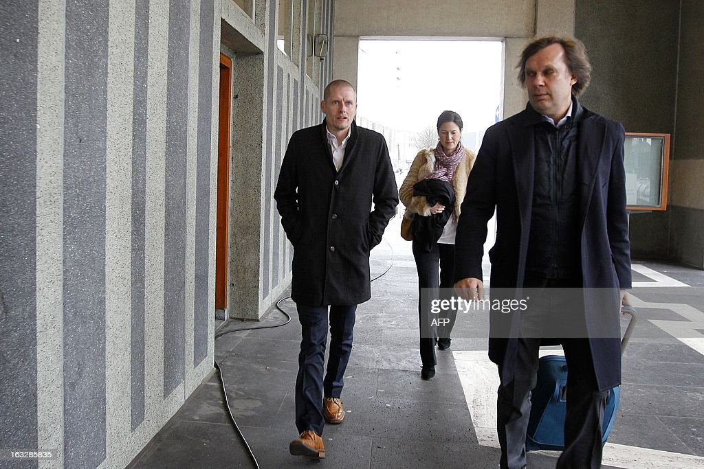 Danish cyclist Michael Rasmussen (L) and his lawyer Andre Brantjes (R) walk to an appeal courtroom in Arnhem, on March 7, 2013. Rasmussen is claiming 5.8 million euros (some 7.55 million US dollars) as damages from his former Rabobank team who dismissed him from the 2007 Tour de France,- when he was wearing the race leader's yellow jersey, after confusion over his whereabouts when it came to anti-doping tests. Rasmussen admitted in January 2013 that he had used banned drugs between 1998-2010. - belgium out