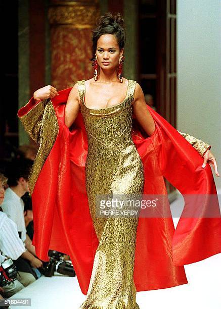Danish designer Erik Mortensen presents a gold lame evening dress with a matching red satinlined coat during the JeanLouis Scherrer 1993/94...