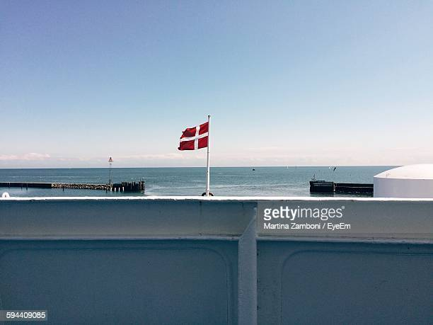 Danish Flag At Seaside Against Clear Sky