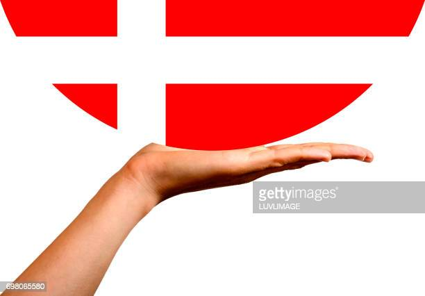 Danish Flag in a hemispere, on the palm of a hand.