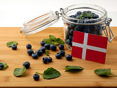Danish flag on a wooden plank with blueberries isolated on white
