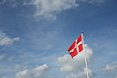 Danish flag in the wind with blue sky