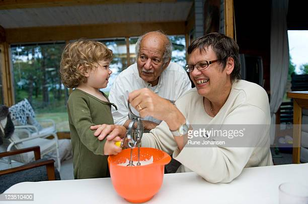 Danish girl, 1 years old, eating whipped cream with her Middle-Eastern grandfather, 77 years old, and Caucasian grandmother, 59 years old, indoors