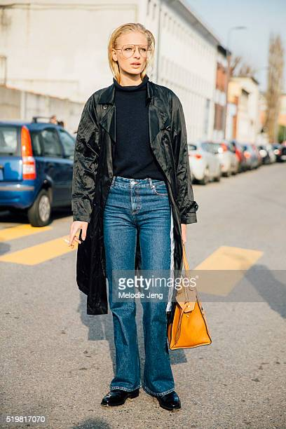 Danish model Frederikke Sofie wears wideframed thin glasses a long black jacket black top flared jeans and a Celine purse after the Pucci show during...