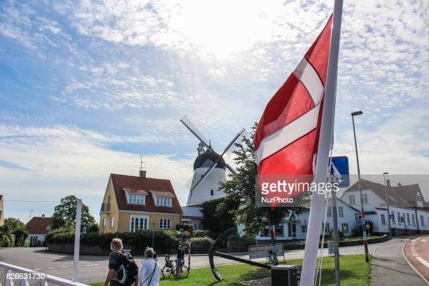 Danish national flag in front of windmill is seen on 2 August 2017 in Gudhjem Bornholm Island Denmark