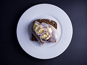 Traditional Danish open faced sandwich (smoerrebroed) with marinated herring, curry sauce and raw onion rings