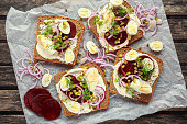 Danish open-face rye sandwich with quail eggs, beetroot, pickled onions and cucumbers drizzled with dill.